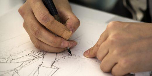 Tjej som skissar på ett papper