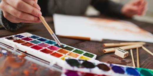 I bakgrunden: en blurrig hand som håller i pensel. I förgrunden: Två färgglada färgpaletter