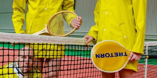 Tre personer iklädda gula regnjackor som står på en tennisbana med varsitt tennisrack