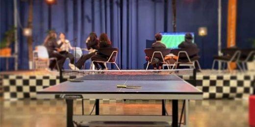 Bild från Fritidsgården Tegelhuset i Rosengård. Ett pingisbord i förgrunden och barn och unga som sitter på en upphöjd scen med ryggen emot och spelar fifa